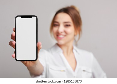 Happy woman showing blank smartphone screen, showing application over grey background