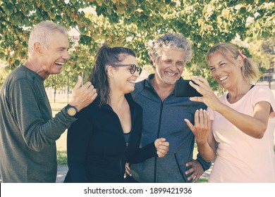 Happy woman showing cellphone screen to fitness club mates. Joyful mature friends standing together after morning exercises in park. Retirement or communication concept