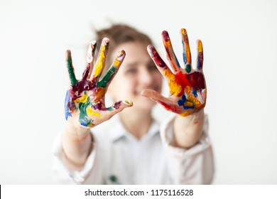 Happy woman showing hands painted in colorful paints on white background. Fun concept