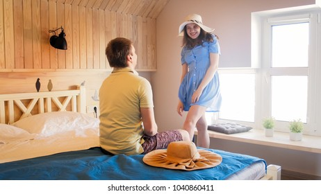 Happy woman showing hats to her husband sitting on bed