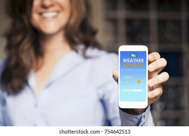 Happy woman showing a mobile phone with weather forecast in the screen.