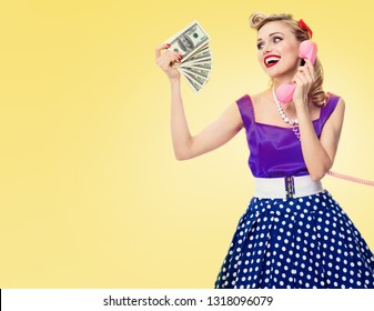 Happy woman showing money cash, talking on phone, in pin-up style dress in polka dot, with copy space area for some slogan or advertising text message, on yellow background. Retro and vintage.