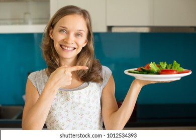 Happy Woman Showing Plate with Sliced Vegetables