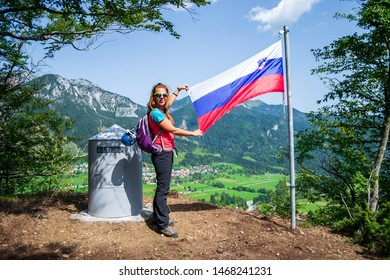 Happy woman showing the Slovenian flag after finishing climbing the via ferrata route on the Grancisce hill, above Mojstrana village. Adventure concept.