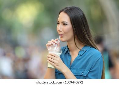 Happy woman sipping milk shake walking in the street