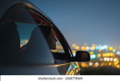 The happy woman sit in a car on the city lights background. evening night time