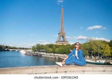 Happy woman sit at river on eiffel tower in paris, france. Woman smile in sunglasses on blue sky. Travelling on summer vacation. Dreaming about paris. Girl with fashion look and sensual beauty.