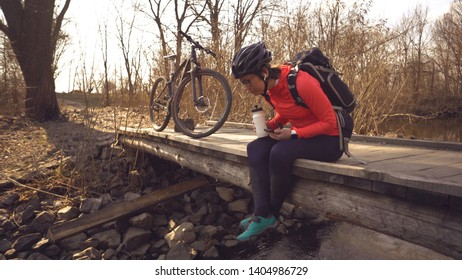 Happy woman sits wooden bridge over river, listening music in headphones with smartphone hands and drinks water white bottle. cyclist listens song in nature. athlete near bike hand on plastic drink.