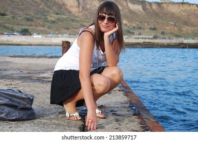 Happy Woman Sitting By The Sea