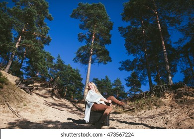 happy woman sitting in a chair on a sandy cliff in the forest