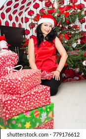 Happy woman sitting in front of Christmas tree with presents in her house
