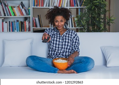 Happy woman sitting at home with remote control watching tv