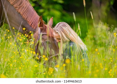 Happy woman sitting in the meadow with her arabian horse