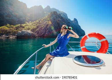 Happy woman sitting on the bow boat in the sea. Water activities.