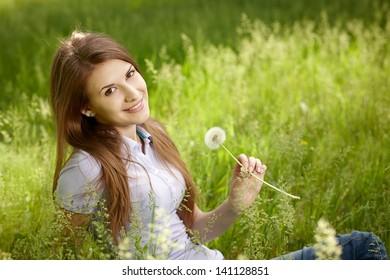 Happy woman sitting on meadow holding white dandelion