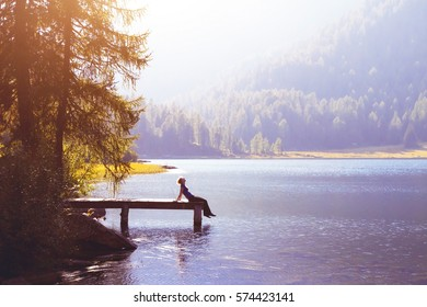 happy woman sitting on the pier and smiling, happiness or inspiration concept, enjoy life - Shutterstock ID 574423141