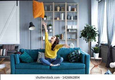 Happy woman sitting on the sofa sitting down with pillow indoors. Home life.