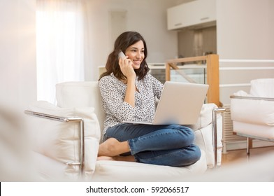 Happy woman sitting on sofa with laptop and talking on phone at home. Young successful businesswoman working from home while talking at phone. College student studying on laptop and using phone.