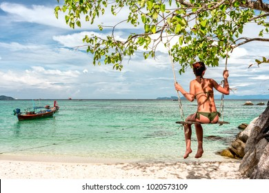 Happy  woman sitting on a swing on the white sand beach by the blue sea in summer of Thailand