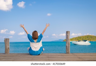 Happy Woman sitting on the wooden bridge with a clear blue sky and sea