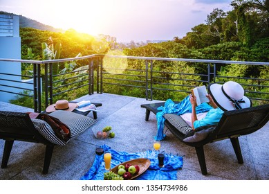 A happy woman sitting reading relaxing book on the balcony at home, summer on holiday drinking wine,orange juice and fruit on the terrace in the at sunset.