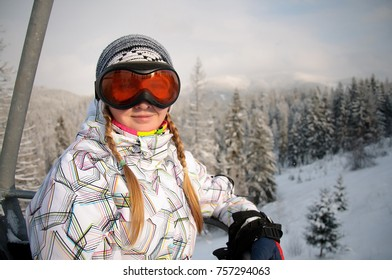 Happy woman in ski eyeglasses rises on the lift in Carpathian mountains. On background of forest and ski slopes. Close up. Winter nature. Heavy snow falls.