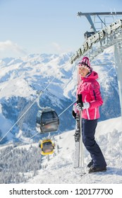 Happy woman in ski goggles against a ski-lift and wonderful winter mountains backgroundagainst wonderful winter mountains background and , Zellertal, Austria