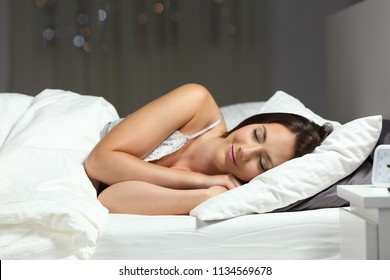 Happy woman sleeping on the bed in the night at home
