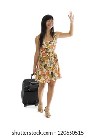 happy woman with small luggage on wheels waving, isolated on white background