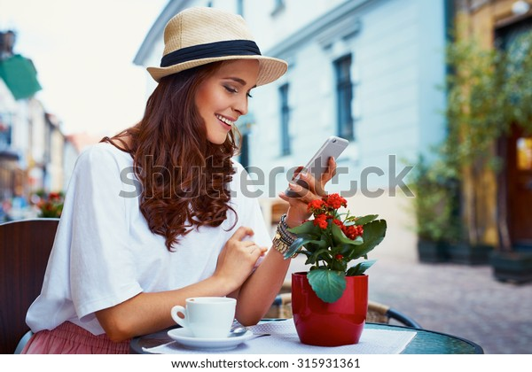 Happy woman with smartphone in outdoor cafe