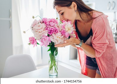 Happy woman smelling bouquet of peonies. Housewife enjoying decor and interior of kitchen. Sweet home. Allergy free