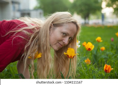 Happy woman smelling a tulip