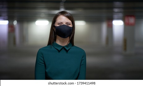 Happy woman smiles in a black mask in an underground parking lot, protecting against virus and infections during an epidemic.
