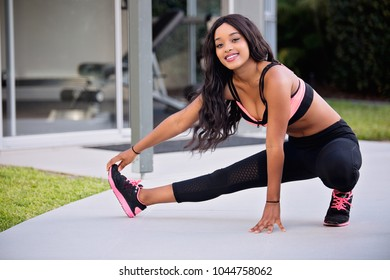 Happy woman smiles gets down low and stretches