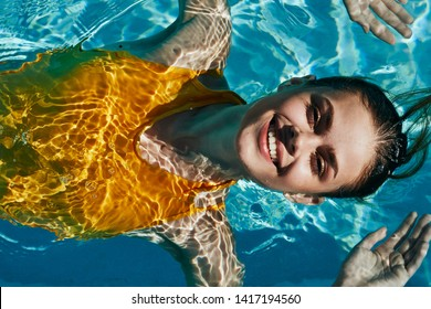Happy woman smiling at camera transparent water yellow swimsuit top view