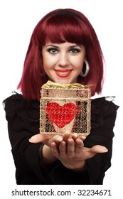 Happy woman smiling with heart packed in a golden gift box in her hand.Shallow DOF, focus on the heart.