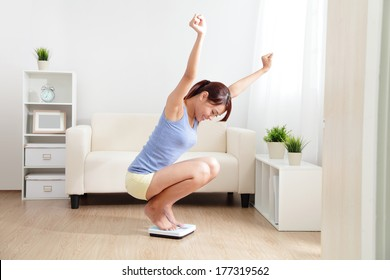 Happy Woman smiling on weighing scales at home, asian