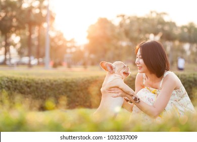 Happy woman and smiling play with a puppy under evening sunset or sunrise in a park.