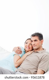 Happy woman snuggling with her husband on couch in living room