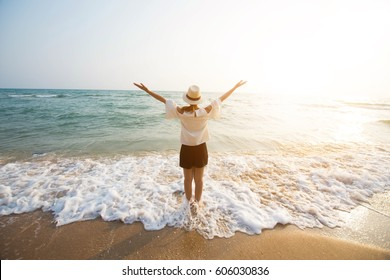 happy woman stand on sand of the sea and show hand in to sky. subject is blurred