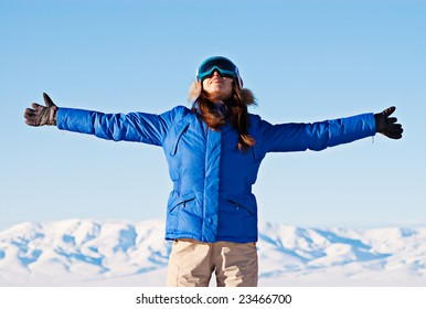 happy woman standing against snowy mountains and blue sky
