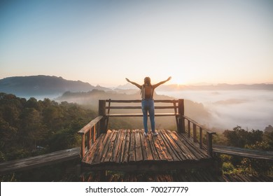 Happy woman standing alone with arms raised up  during beautiful sunrise at the morning.Enjoying with nature