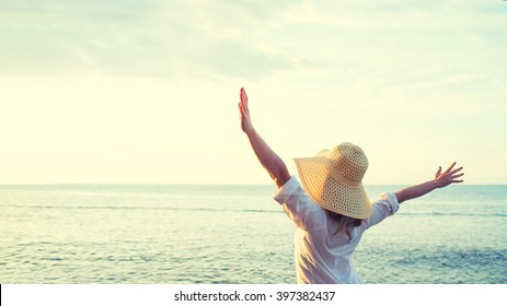 Happy woman standing arms outstretched back and enjoy life on the beach at Sea