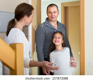 Happy woman standing at doorway and inviting guests to come inside. Focus on girl