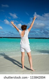 Happy woman standing with her arms out stretched on a tropical beach. Composed in the middle of the image.