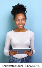 Happy woman standing with ipad looking at the camera and happily smile closeup