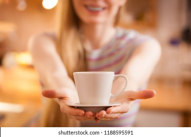 Happy woman standing in kitchen holding cup of tea of coffee enjoying her relaxing free time.