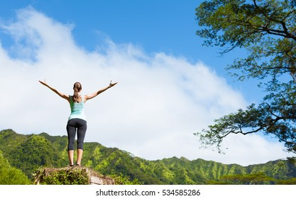 Happy woman standing on a mountain with her arms up in the air feeling happy and free.