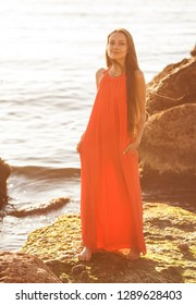 happy woman standing on a stone near the sea. girl with long natural hair in a red sundress