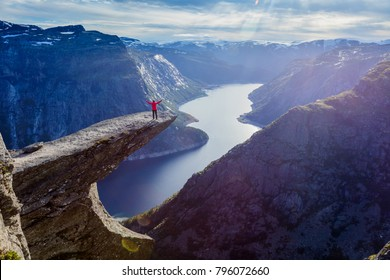 Happy Woman standing on Trolltunga in Norway